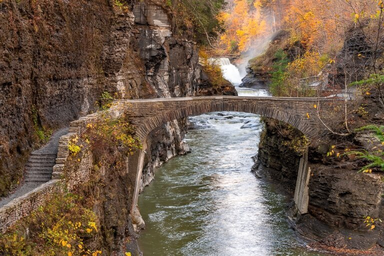 Letchworth State Park NY stone bridge crossing the Genesee River and Lower Falls waterfall in the background fall foliage colors photography