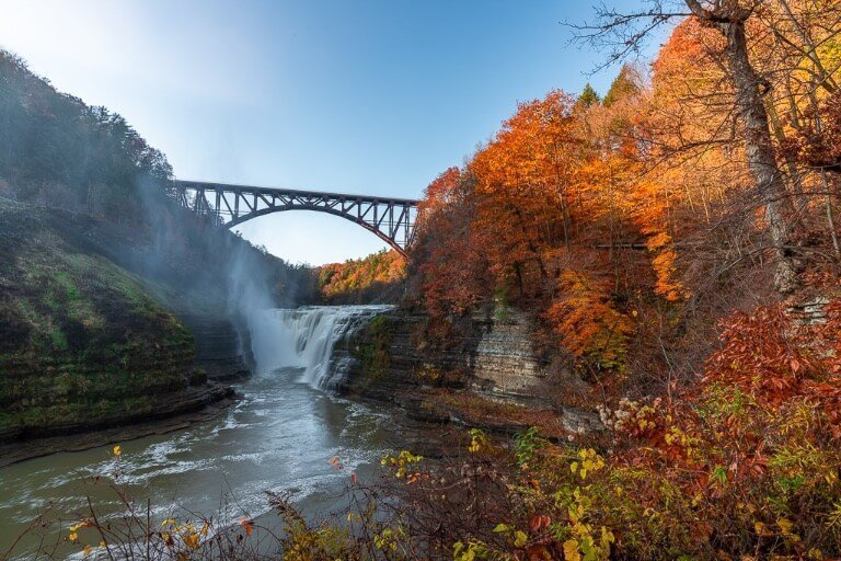 Letchworth State Park Upper Falls in autumn with stunning fall foliage blue sky and awesome waterfall
