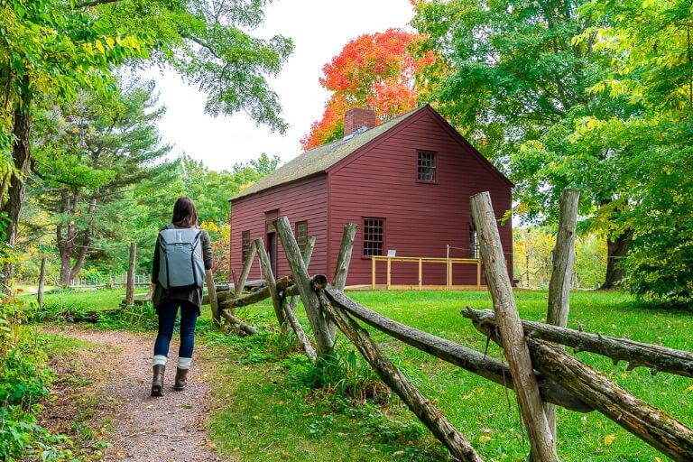 Kristen walking on a path through lush green farm with barn and red trees