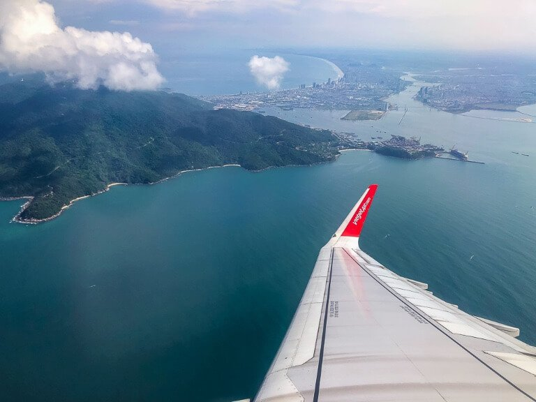 Airplane wing over the ocean and islands on the way from vietnam to hong kong
