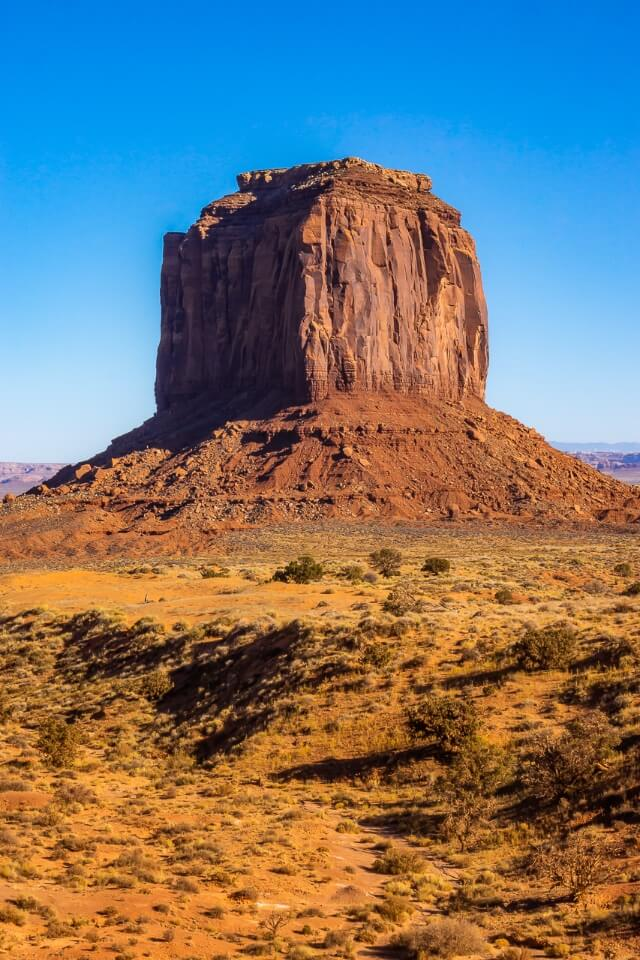 Single butte protruding out of the arizona desert at monument valley