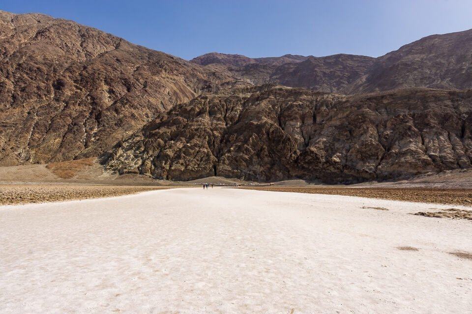 Badwater Basin is the most famous place to visit in death valley national park california white salt flat ground below sea level and huge rocks behind