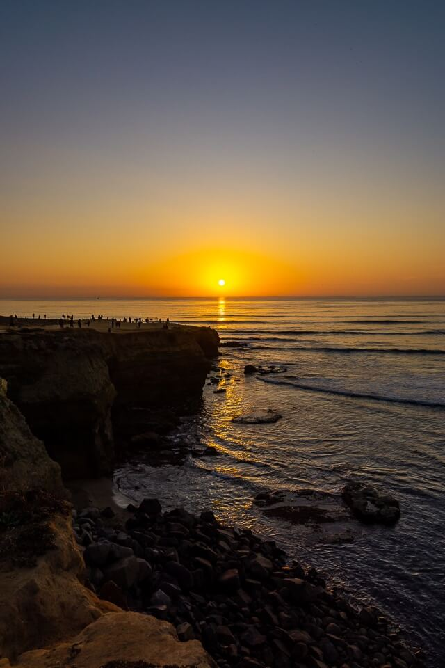 Stunning California sunset at sunset cliffs in san diego sunlight reflecting on pacific ocean and clear purple sky