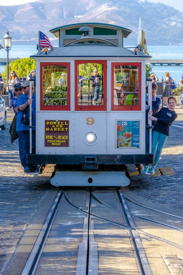 famous cable car of san francisco with tourists hanging off the sides san francisco bay in background