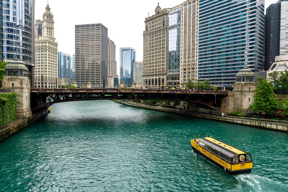 Turquoise river in chicago with yellow boat and skyscrapers