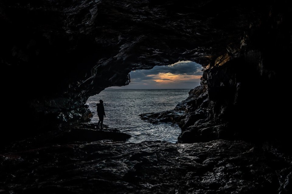 Kristen inside a cave silhouetted against the sunrise outside the cave at acadia national park maine usa