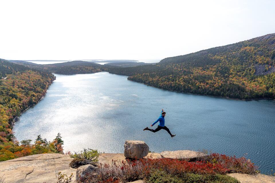 Mark jumping between rocks perspective against lake at acadia national park maine usa
