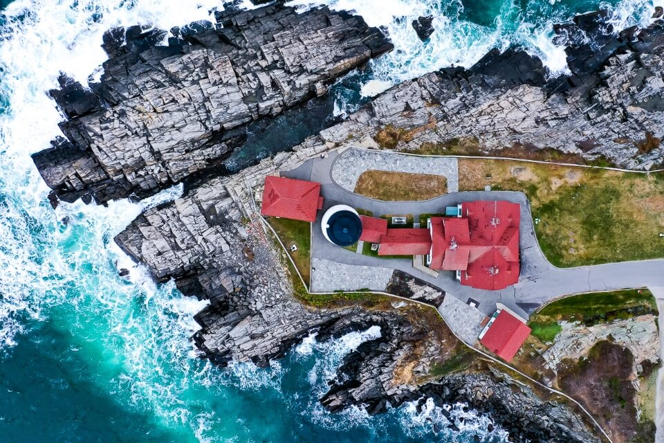 Birds eye view drone photography of portland lighthouse in maine awesome picture of america turquoise waters waves crashing and entire lighthouse plot