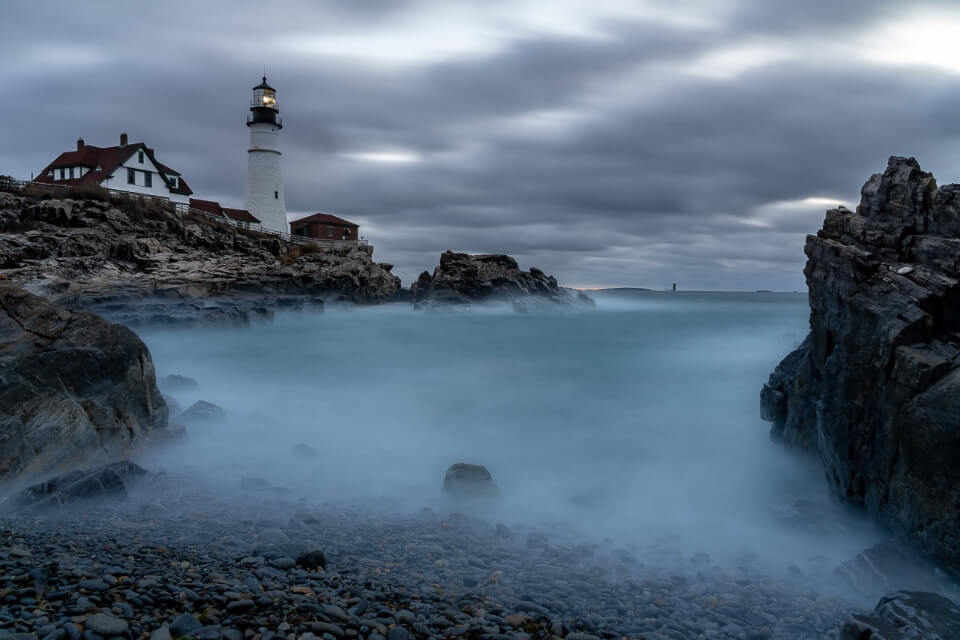 Sunrise at portland head lighthouse with long exposure on water creating cloudy effect maine photography