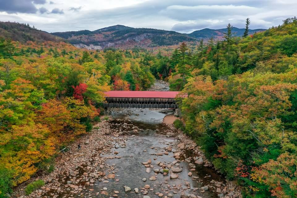 Drone picture of covered bridge crossing river on kancamagus highway in new hampshire america stunning red bridge surrounded by trees and hills in background