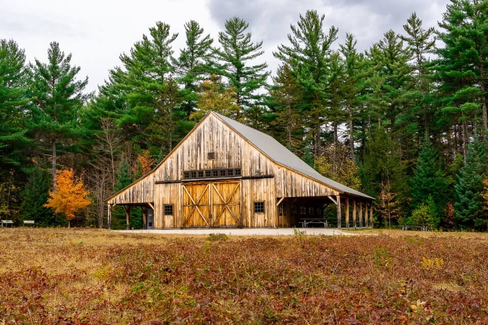 Stunning wooden barn backed by green trees along kancamagus highway scenic drive in new hampshire usa