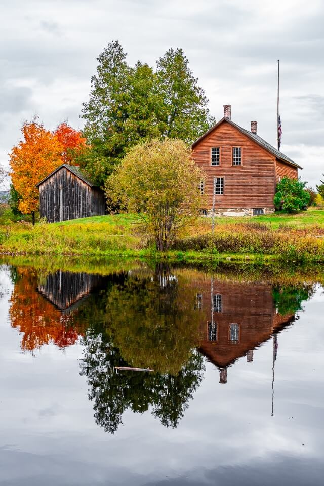 Wooden house barn and trees reflecting perfectly in a small lake museum near ski jump in lake placid new york adirondacks photography