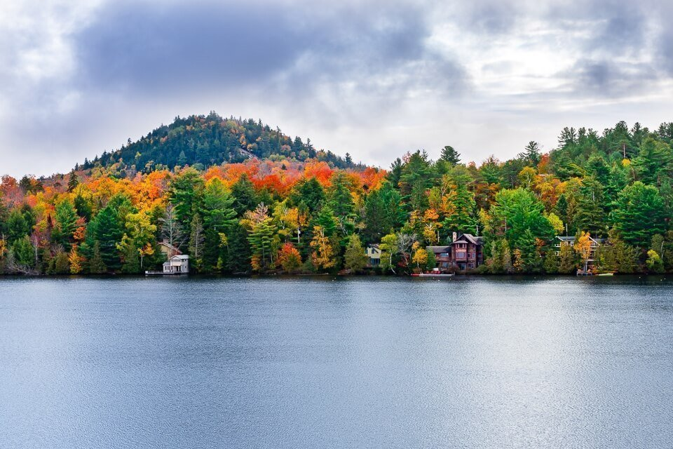 Mirror Lake in Lake Placid New York stunning colors in fall and blue grey lake with dense clouds