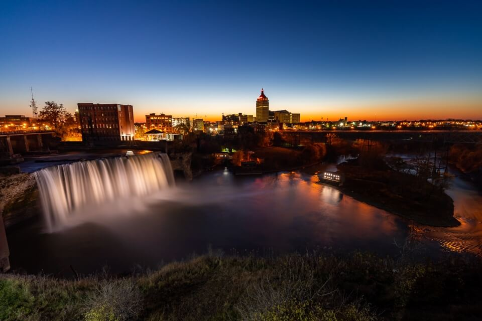 High falls in rochester new york at sunset with stunning colors in the sky and awesome waterfall illuminated