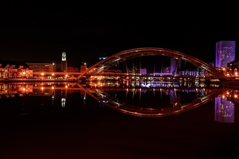 Rochester new york city center at night bridge and building colors reflecting in Genesee river