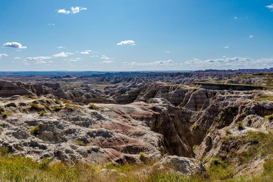 Badlands national park in south dakota with open blue sky and intriguing rocks makes for awesome usa photos