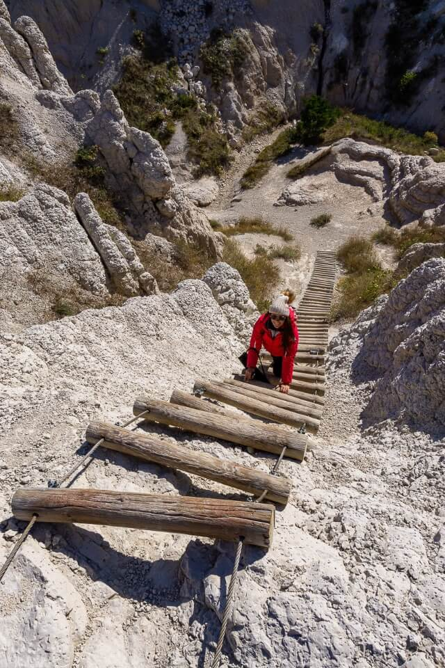 Kristen climbing a long ladder on the notch trail at badlands national park south dakota