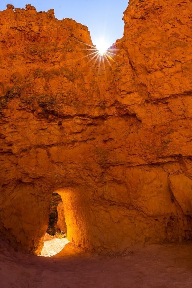 Small arched door carved into huge orange slab of rock and sun starburst at bryce canyon national park utah usa