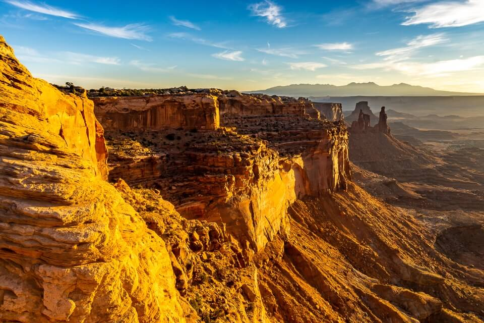 sunrise over stunning rock gorge in canyonlands national park utah usa rock face lit up by sun and blue sky