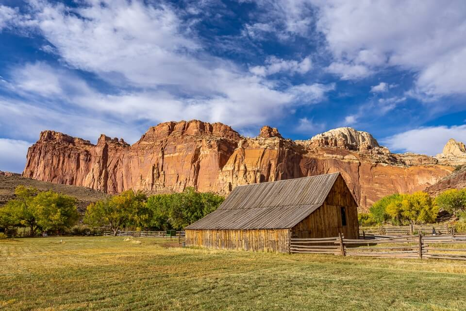Capitol Reef national park in utah america has a stunning picture of fruita barn with orange rocks behind