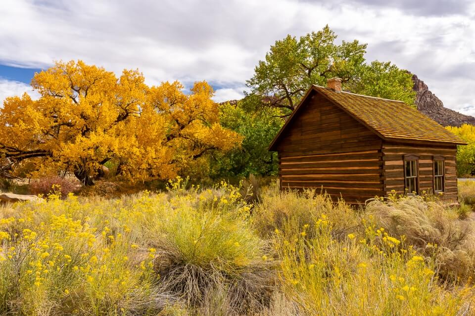 Fruita schoolhouse tiny wooden building surrounded by stunning fall foliage colors in capitol reef national park utah usa