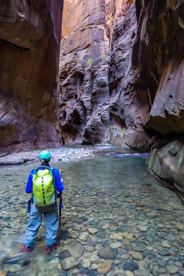 Kristen in full waterproof gear in the virgin river hiking the narrows trail at zion national park utah usa