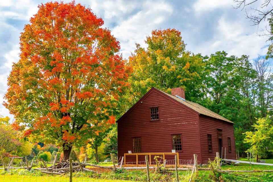 Gorgeous wooden barn with amazing fall foliage colors greens reds vermont photography