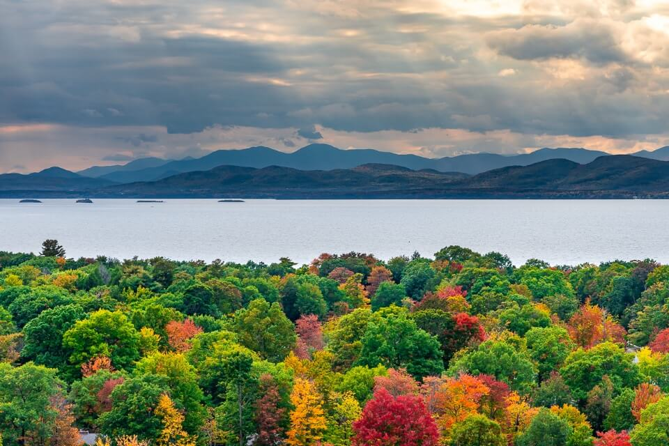 Amazing fall foliage trees lake mountains and sky picture of burlington vermont america with sun rays shining through clouds stunning image