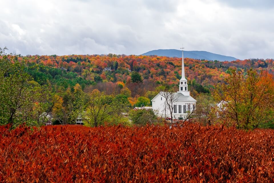 Famous white church in stowe vermont with stunning burnt red foliage in foreground and hills in background filled with trees amazing pictures of america