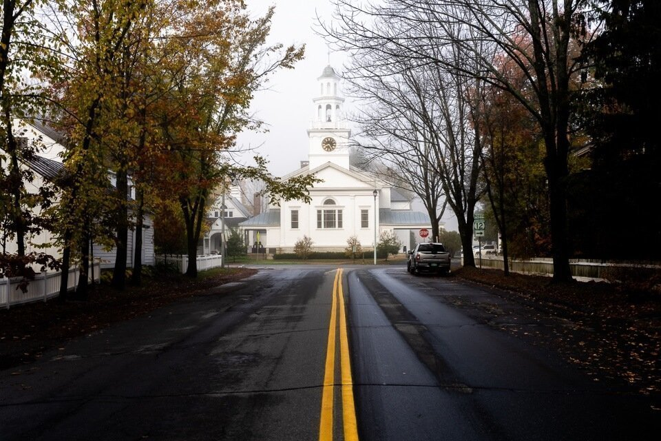 Eerie photo of a white church with dark road leading up in woodstock vermont misty image
