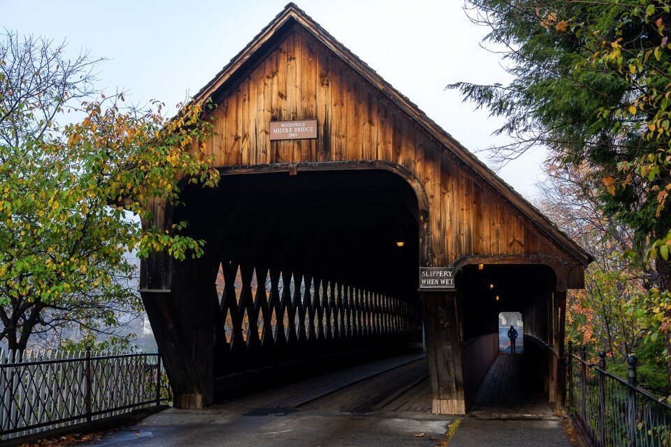 Beautiful covered bridge in downtown woodstock vermont man silhouetted against entrance to pedestrian walkway