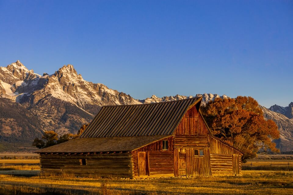 TA Moulton barn mormon row grand teton national park wyoming is one of the most photographed pictures of america amazing scenery photo opportunities with mountains in background at sunrise
