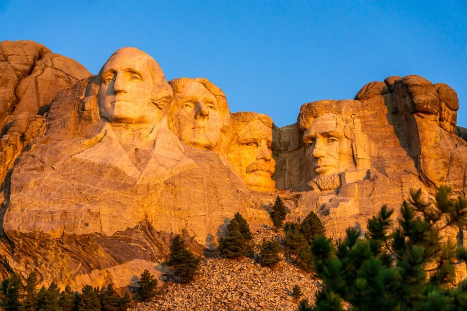 Mount Rushmore turning brilliant orange as the low sun lights up one of the most iconic pictures of all in america