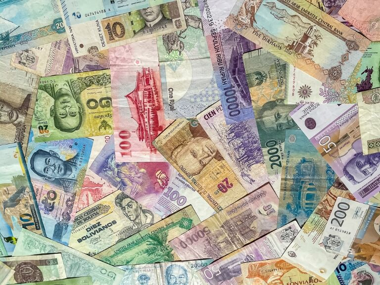Money currency from around the world - it is difficult to save for travel and a long trip