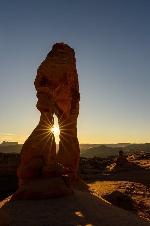 Delicate Arch starburst with the sunset looking incredible in utah arches national park after hiking to the summit