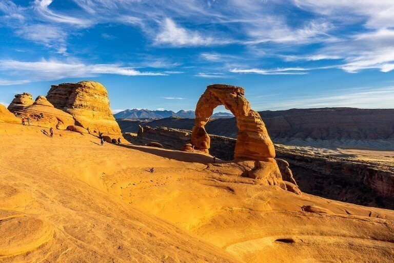 First time you see Delicate Arch from the delicate arch hike just before sunset the orange rocks glowing and blue sky contrasting