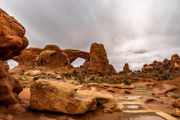 North and South Windows one of the most popular hikes in arches national park with a grey sky and orange rocks in utah