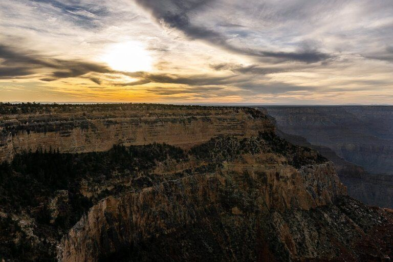 Sun setting over a cliff with sun behind clouds in arizona