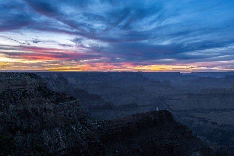 Sunset at Hopi Point in grand canyon south rim bright colors in sky turning to blue at dusk
