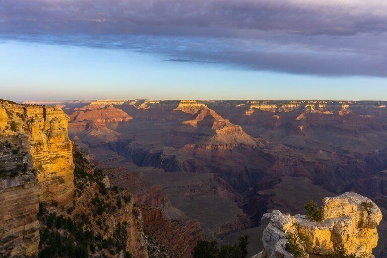 Mather Point from the Rim as the sun is rising and lighting up the canyon floor with clouds turning purple