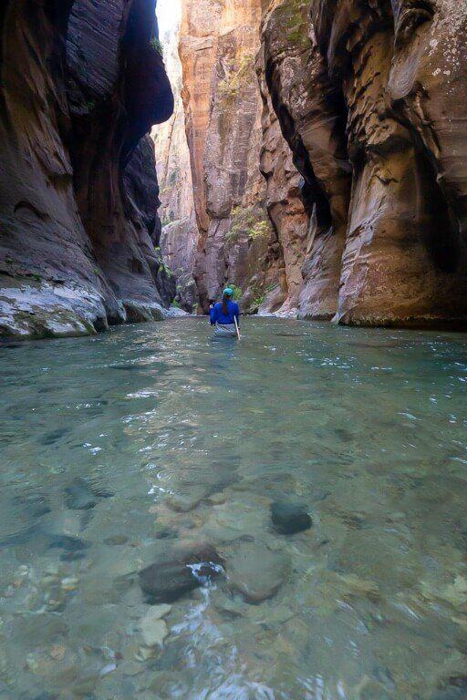 Kristen waist deep in the virgin river between canyon walls in utah