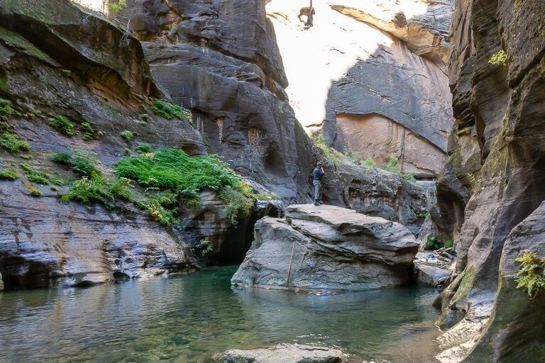 Mark climbing on a huge boulder to continue the hike further into the Narrows in zion national park utah