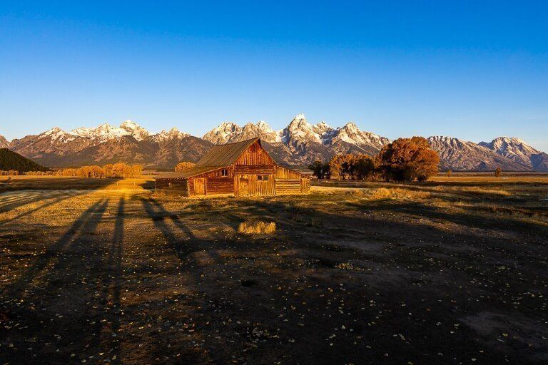 Field with wooden building and mountains