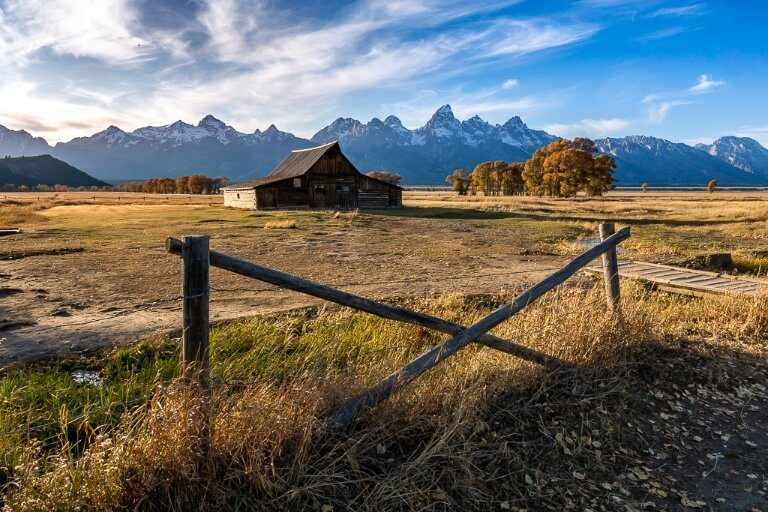 TA Moulton Barn on mormon row in grand teton national park at sunset behind a fence
