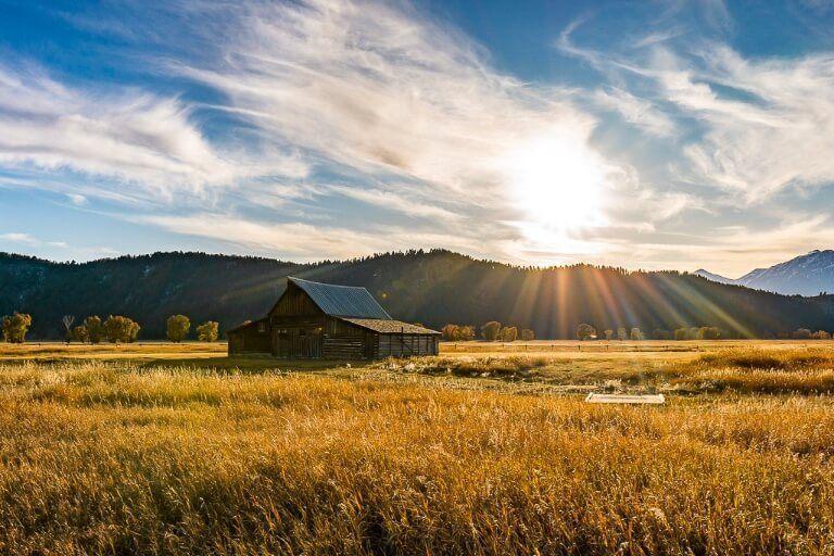 TA Moulton barn sunset mormon row grand teton national park starburst gorgeous field and blue sky