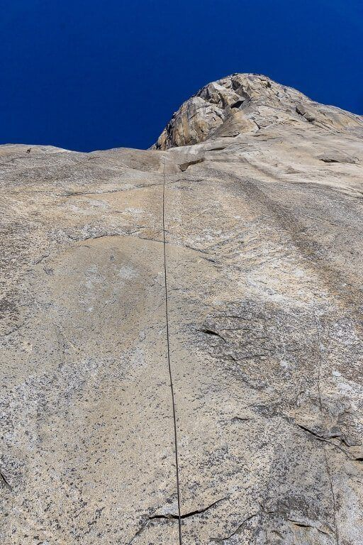 El Capitan climbing wall from directly at the bottom with a rope and climber in the top left of the picture