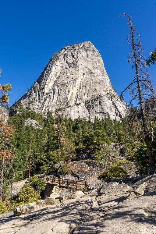 Liberty Cap granite dome behind green trees a wooden bridge and granite boulders hiking trail yosemite national park photography