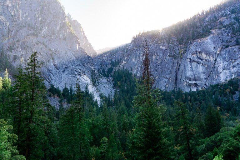 Starburst with the sun appearing over a granite wall with dense green trees in a valley and hazy sky Mist trail photography in yosemite national park california
