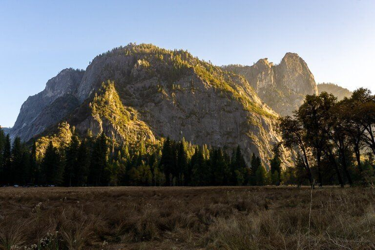 Sunset over looming granite dome with meadow in shadow foreground stunning yellows