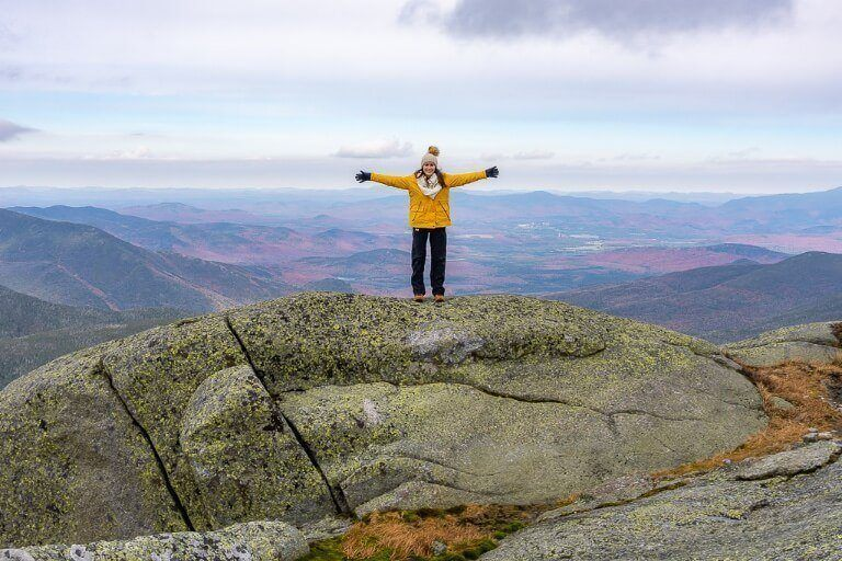Woman with arms outstretched celebrating reaching the highest point in new york mount marcy adirondack high peaks